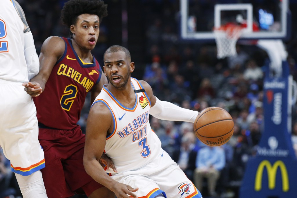 Oklahoma City Thunder guard Chris Paul (3) drives around Cleveland Cavaliers guard Collin Sexton (2) during the first half of an NBA basketball game W...