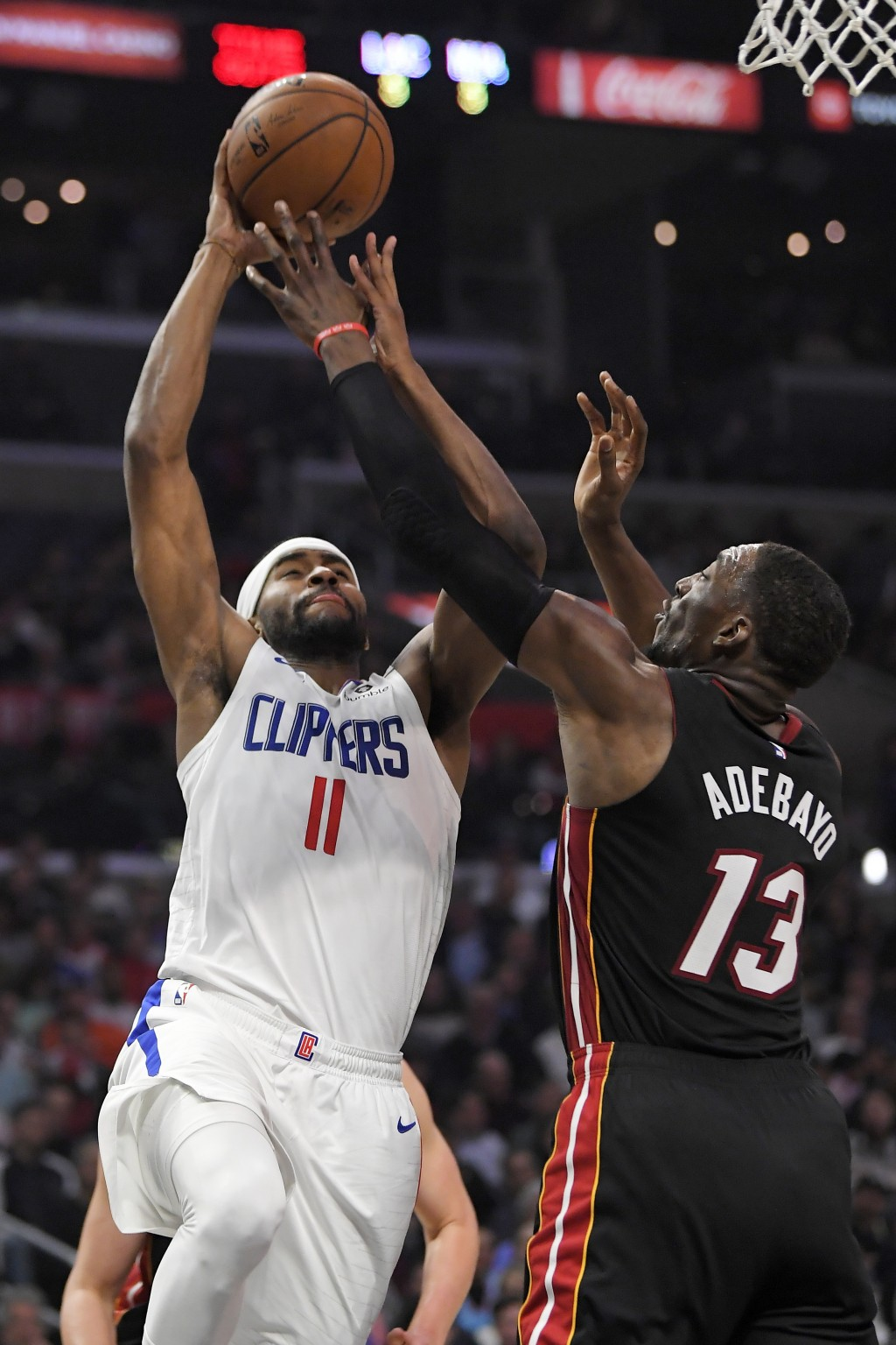 Los Angeles Clippers forward Maurice Harkless, left, shoots as Miami Heat forward Bam Adebayo defends during the first half of an NBA basketball game ...