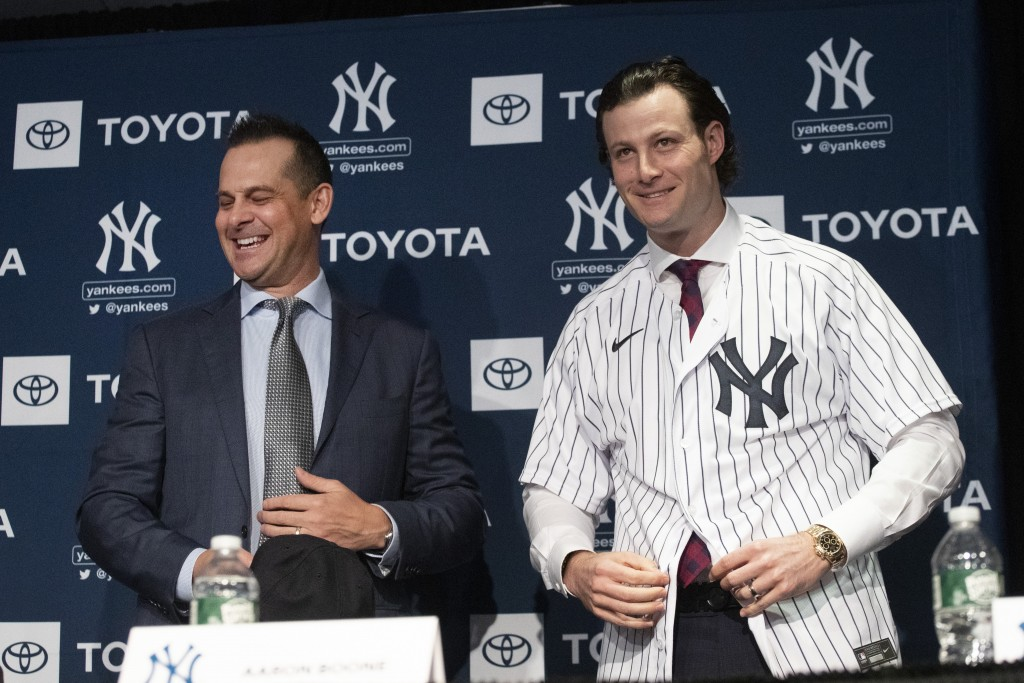 FILE - In this Dec. 18, 2019, file photo, New York Yankees manager Aaron Boone, left, smiles as Gerrit Cole tries on a Yankee jersey as he is introduc...