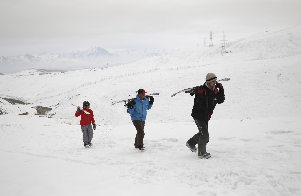 In this Friday, Jan. 24, 2020, photo, a group of snowboarders hike up the snow-covered hillside known as Kohe Koregh, on the outskirts of Kabul, Afgha...
