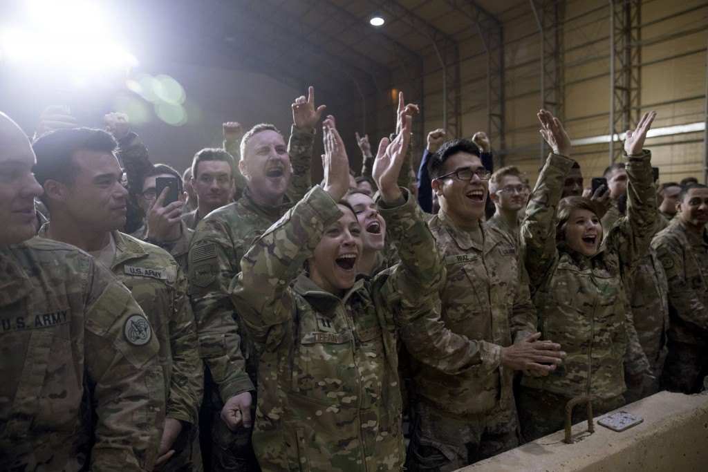 FILE - In this Dec. 26, 2018 file photo, members of the U.S. military cheer as President Donald Trump speaks at a hangar rally at Al Asad Air Base, Ir...
