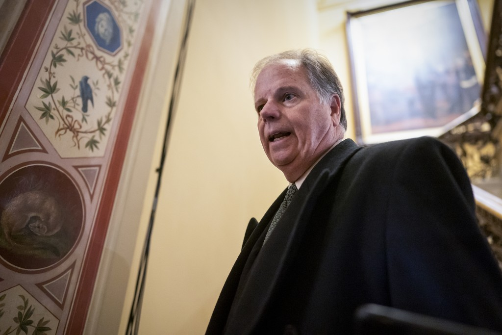 FILE - In this Jan. 31, 2020 file photo, Sen. Doug Jones, D-Ala., is questioned by reporters as he arrives at the Capitol for the impeachment trial of...