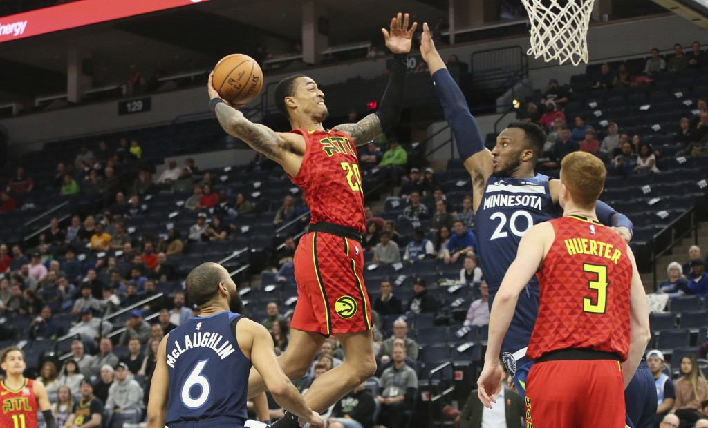 Atlanta Hawks' John Collins, center left, goes up for a shot as Minnesota Timberwolves' Josh Okogie of Nigeria defends in the second half of an NBA ba...