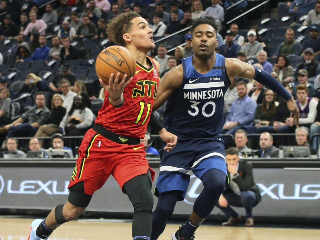 Atlanta Hawks' Trae Young, left, drives past Minnesota Timberwolves' Kelan Martin in the second half of an NBA basketball game Wednesday, Feb. 5, 2020...
