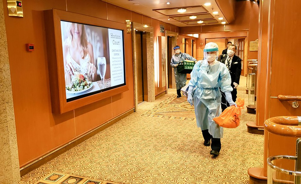 In this Tuesday, Feb. 4, 2020, photo taken by the passenger, medical workers in protective suits walk on the cruise ship Diamond Princess anchored off...