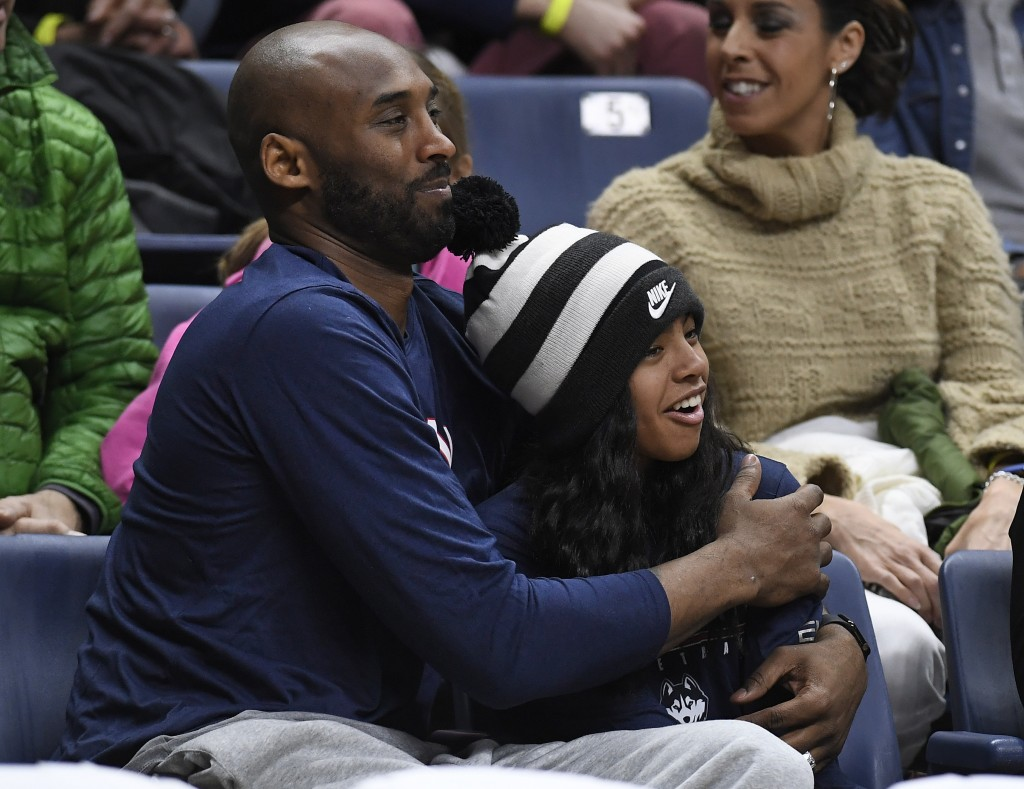 FILE - In this March 2, 2019, file photo Kobe Bryant and his daughter Gianna watch the first half of an NCAA college basketball game between Connectic...