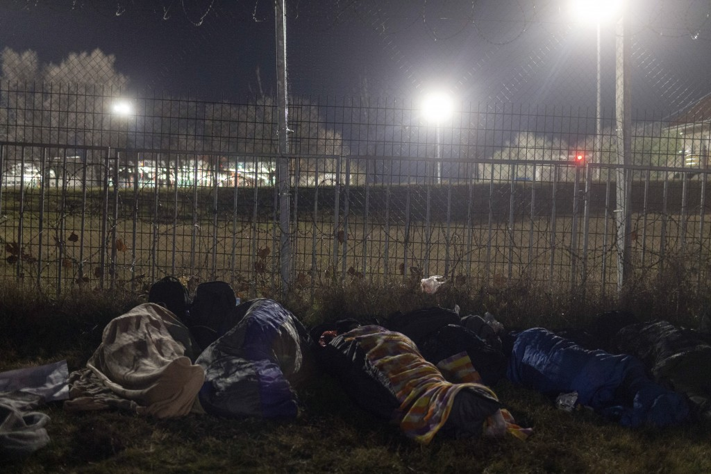 People wrapped in blankets sleep at the border line between Serbia and Hungary in Kelebija, Serbia, Thursday, Feb. 6, 2020. About two hundred migrants...