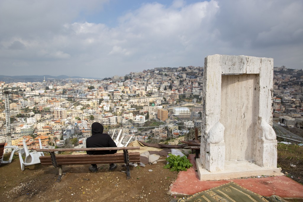 In this Tuesday, Feb. 4, 2020, photo, an Israeli Arab youth sits at a view point overlooking the Israeli Arab town of Umm al-Fahm. President Donald Tr...