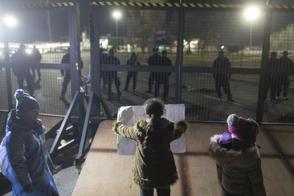 Children stand at the border line between Serbia and Hungary in Kelebija, Serbia, Thursday, Feb. 6, 2020. About two hundred migrants, including childr...