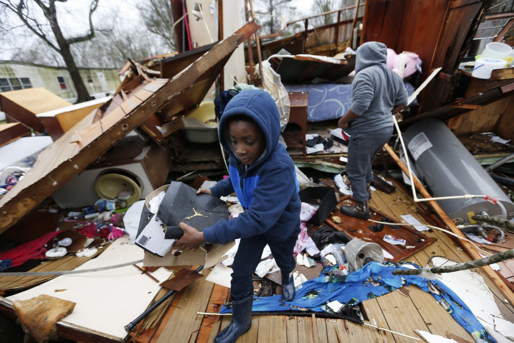 Emma Carter's grandsons comb the remains of her mobile home in Pickens, Miss., looking for salvageable clothing and personal items after severe weathe...