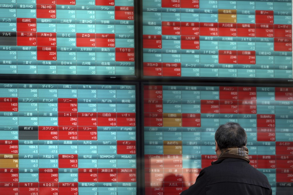 A man looks at an electronic stock board showing Japan's Nikkei 225 index at a securities firm in Tokyo, Friday, Feb. 7, 2020. Asian stock markets hav...