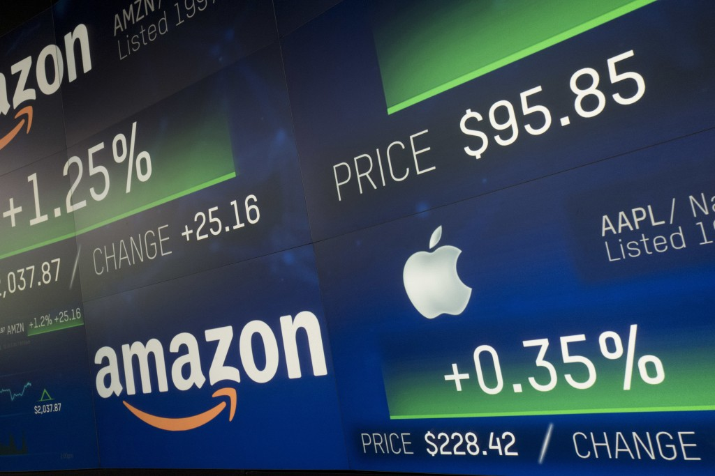 FILE- In this Sept. 4, 2018, file photo Amazon and Apple stock prices are shown on an electronic screen at the Nasdaq MarketSite in New York. Accordin...