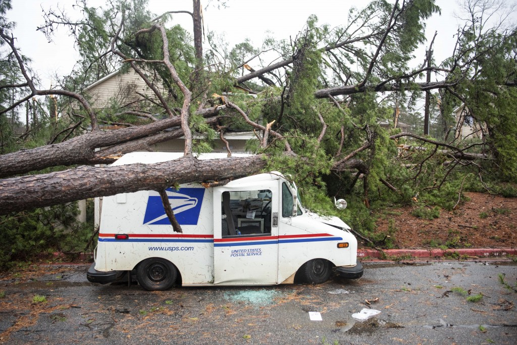 CORRECTS YEAR TO 2020 NOT 2019 - Fallen trees rest on a damaged postal truck at an apartment complex where a reported tornado passed through Thursday,...