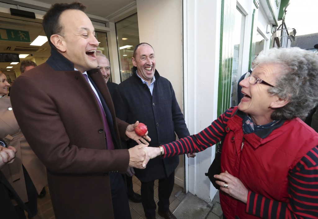 Ireland's Prime Minister Leo Varadkar, left, and Fine Gael candidate Pat Deering, share a joke with Patricia Cremin Hegerty after she handed the Taois...