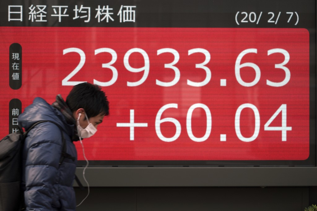 A man walks past an electronic stock board showing Japan's Nikkei 225 index at a securities firm in Tokyo, Friday, Feb. 7, 2020. Asian stock markets h...