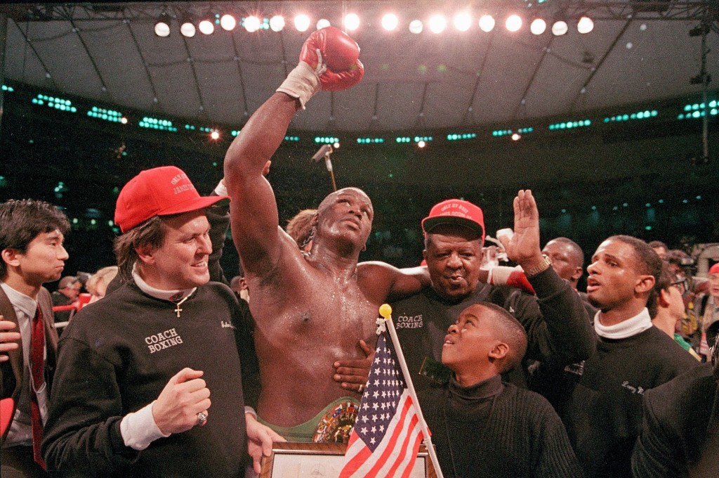 "FILE - In this Feb. 11, 1990, file photo, heavyweight boxer James ""Buster"" Douglas waves his gloved hand to the cheering crowd as he makes his way to ..."