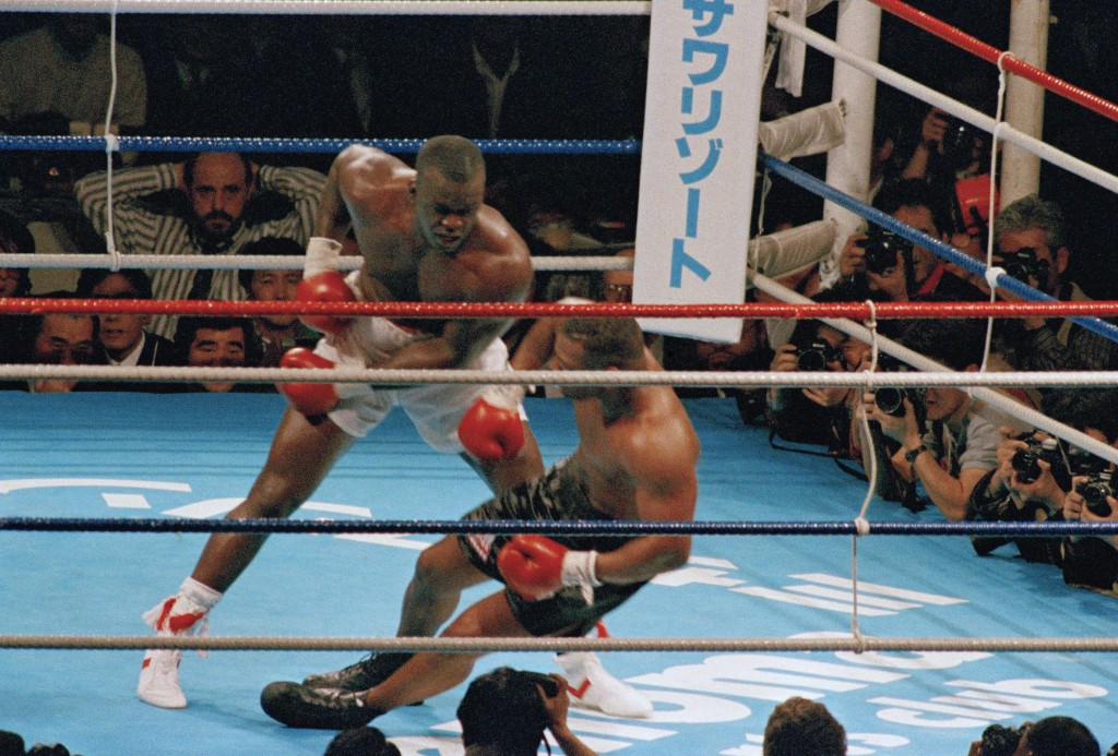 FILE - In this Feb. 11, 1990, file photo, James Douglas, left, follows with a left, dropping Mike Tyson to the canvas in the 10th round of scheduled 1...