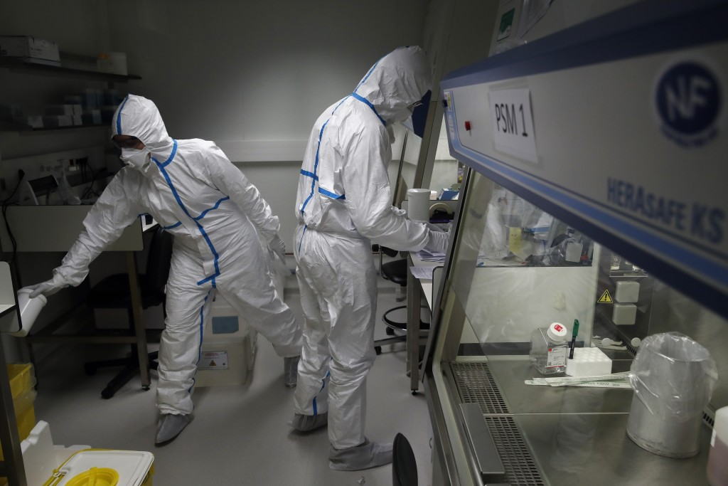 French lab scientists in hazmat gear inserting liquid in test tube manipulate potentially infected patient samples at Pasteur Institute in Paris, Thur...