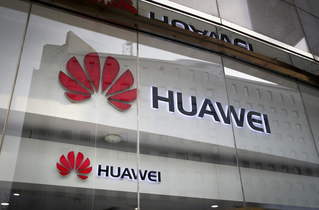 FILE - In this Jan. 29, 2019, file photo, the logos of Huawei are displayed at its retail shop window reflecting the Ministry of Foreign Affairs offic...