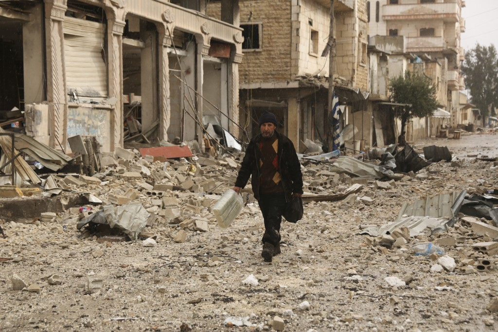 A man carries his belongings through a street destroyed in recent bombings by the Syrian government forces in the town of Sarmin, in Idblib province, ...