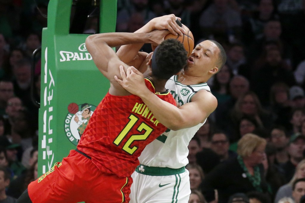Boston Celtics forward Grant Williams and Atlanta Hawks forward De'Andre Hunter (12) vie for a rebound during the first half of an NBA basketball game...