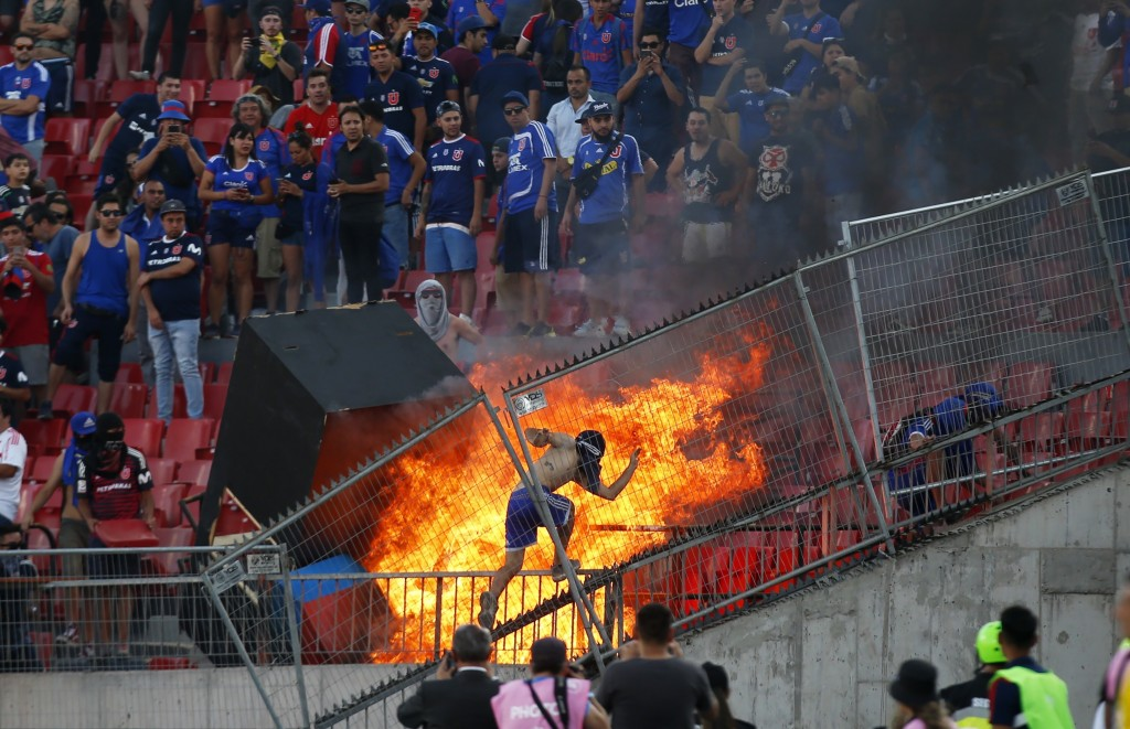 A group of anti-government protesters set fire in a section of the stadium during the Copa Libertadores soccer game between Universidad de Chile and B...