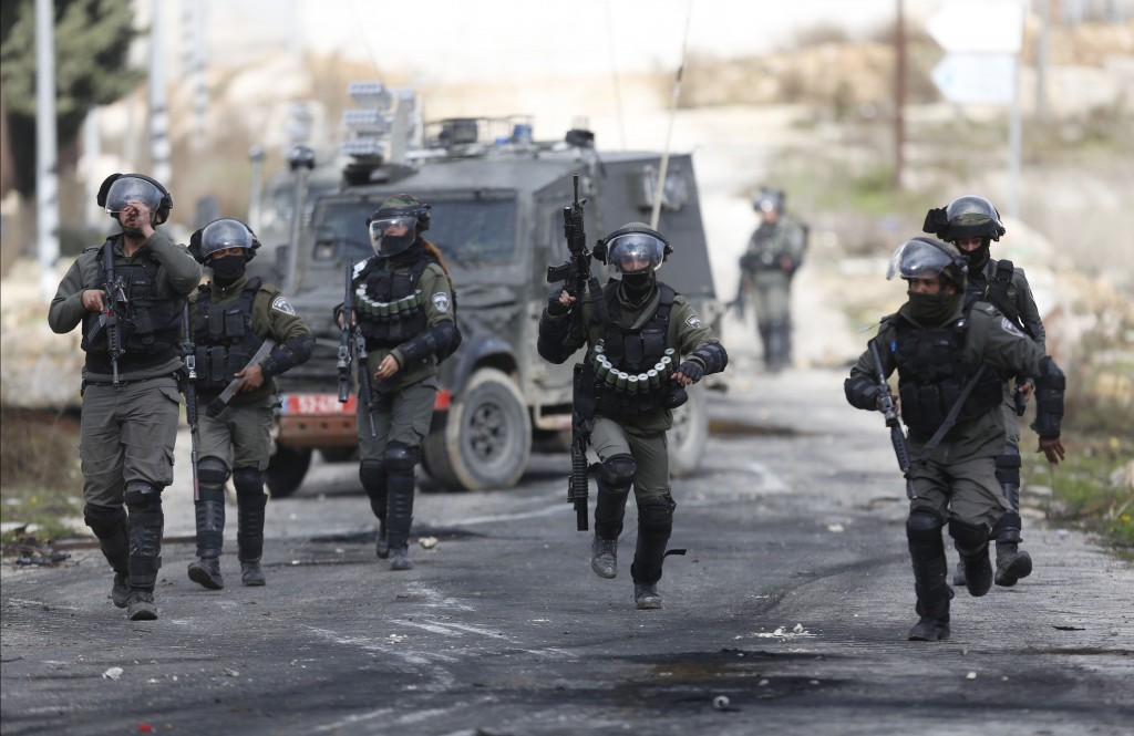 Israeli border police run to take positions during clashes with Palestinian demonstrators protesting the Middle East peace plan announced Tuesday by U...