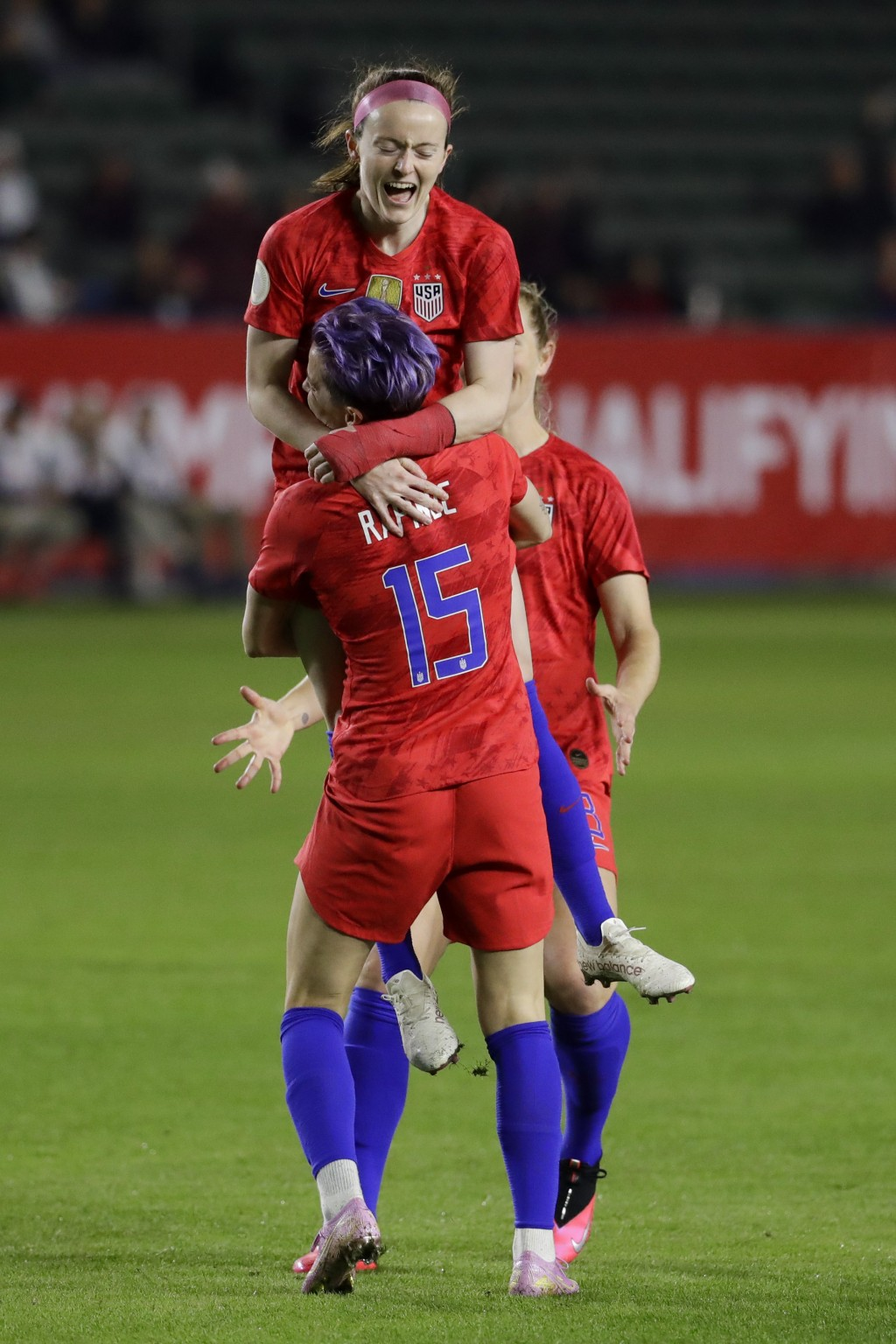 U.S. midfielder Rose Lavelle, top, celebrates with forward Megan Rapinoe after scoring against Mexico during the first half of a CONCACAF women's Olym...