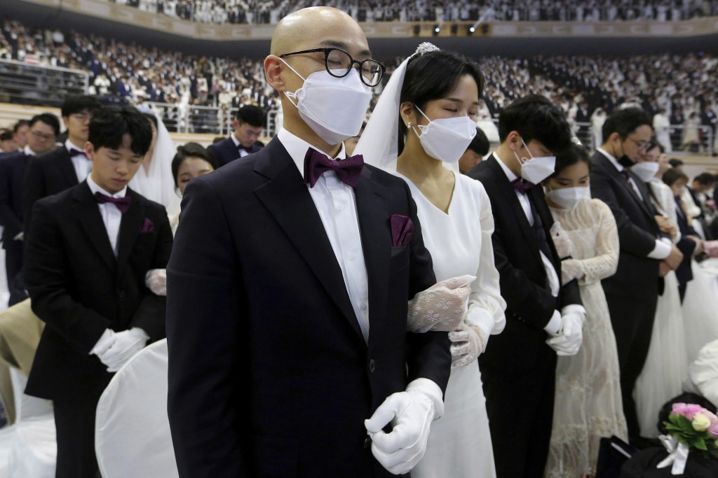 Couples from around the world, some wearing masks, pray during a mass wedding ceremony at the Cheong Shim Peace World Center in Gapyeong, South Korea,...