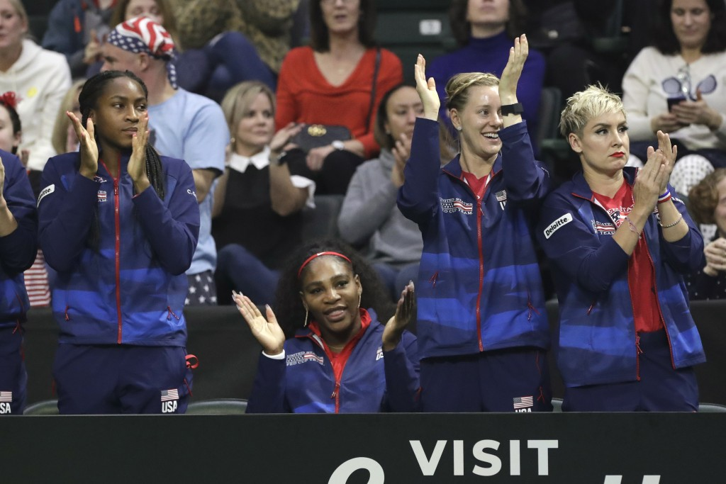 United States' Coco Gauff, left, Serena Williams, seated, Alison Riske and Bethanie Mattek-Sands, right, cheer for teammate Sofia Kenin during a Fed C...