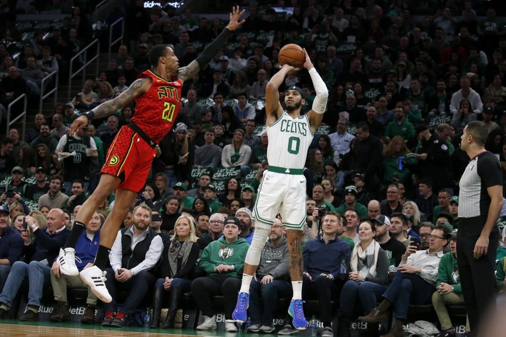 Boston Celtics forward Jayson Tatum (0) shoots a 3-pointer against Atlanta Hawks forward John Collins (20) during the first half of an NBA basketball ...
