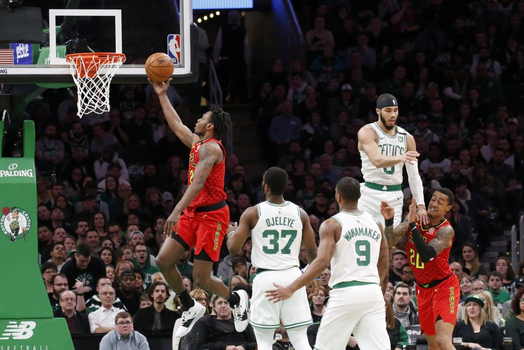 Atlanta Hawks guard Treveon Graham drives to the basket ahead of Boston Celtics defenders during the first half of an NBA basketball game, Friday, Feb...