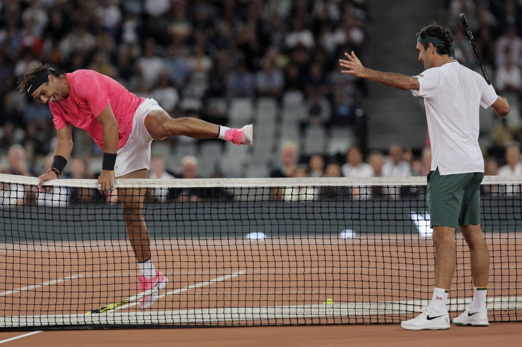 Rafael Nadal, left, jumps the net while Roger Federer watches on during their exhibition tennis match held at the Cape Town Stadium in Cape Town, Sout...