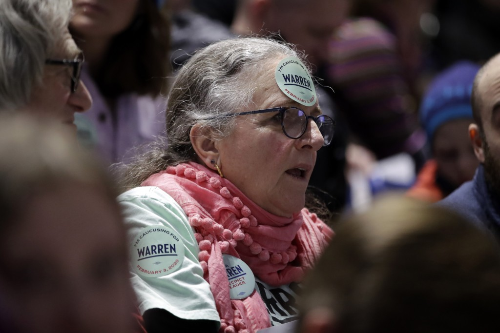 In this Feb. 3, 2020, photo, a woman caucusing for Democratic presidential candidate Sen. Elizabeth Warren, D-Mass., sits in the Warren section at the...