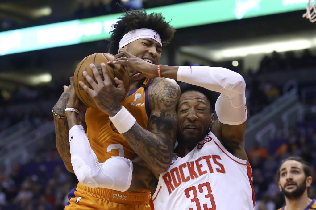 Phoenix Suns forward Kelly Oubre Jr., left, pulls a rebound away from Houston Rockets forward Robert Covington (33) as Suns guard Ricky Rubio, right, ...