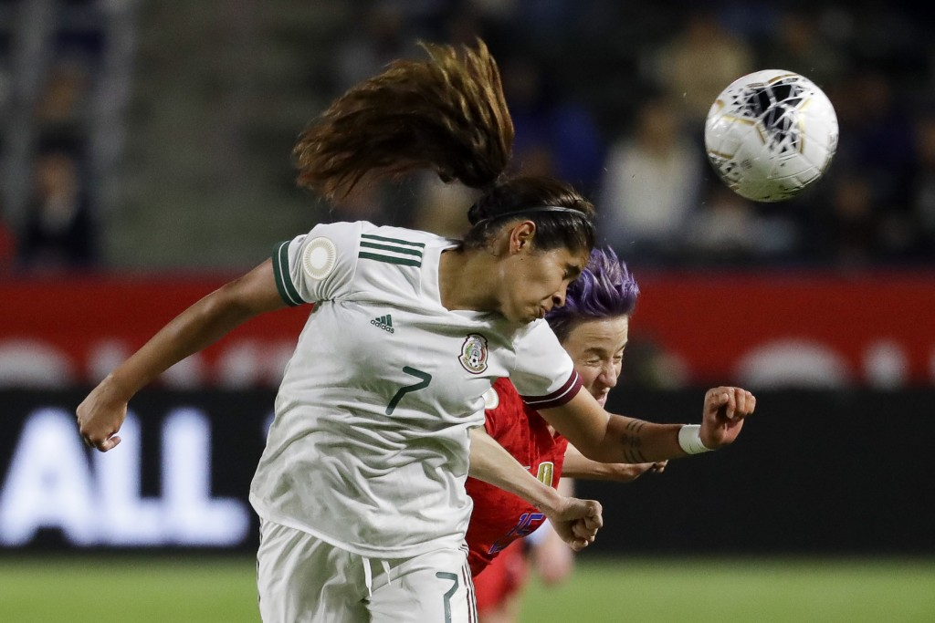 Mexico forward Daniela Espinosa, left, heads the ball away from U.S. forward Megan Rapinoe during the first half of a CONCACAF women's Olympic qualify...