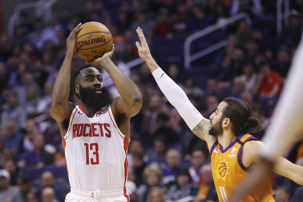 Houston Rockets guard James Harden (13) shoots a three-point basket over Phoenix Suns guard Ricky Rubio, right, during the first half of an NBA basket...