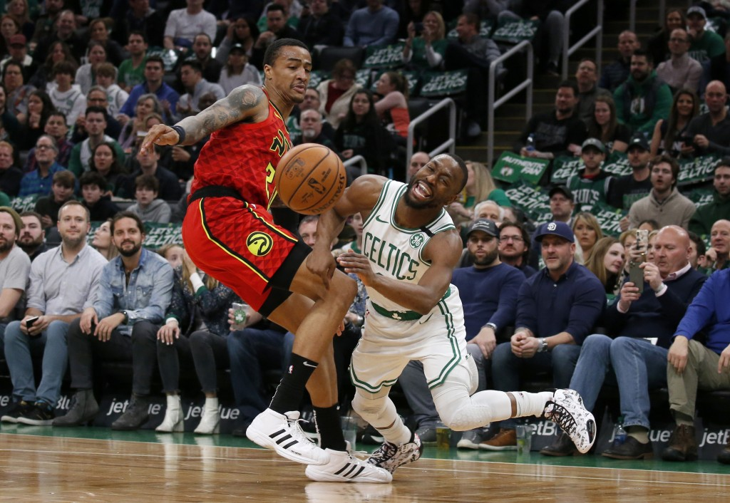 Boston Celtics guard Kemba Walker, right, reacts as he is fouled by Atlanta Hawks forward John Collins during the first half of an NBA basketball game...