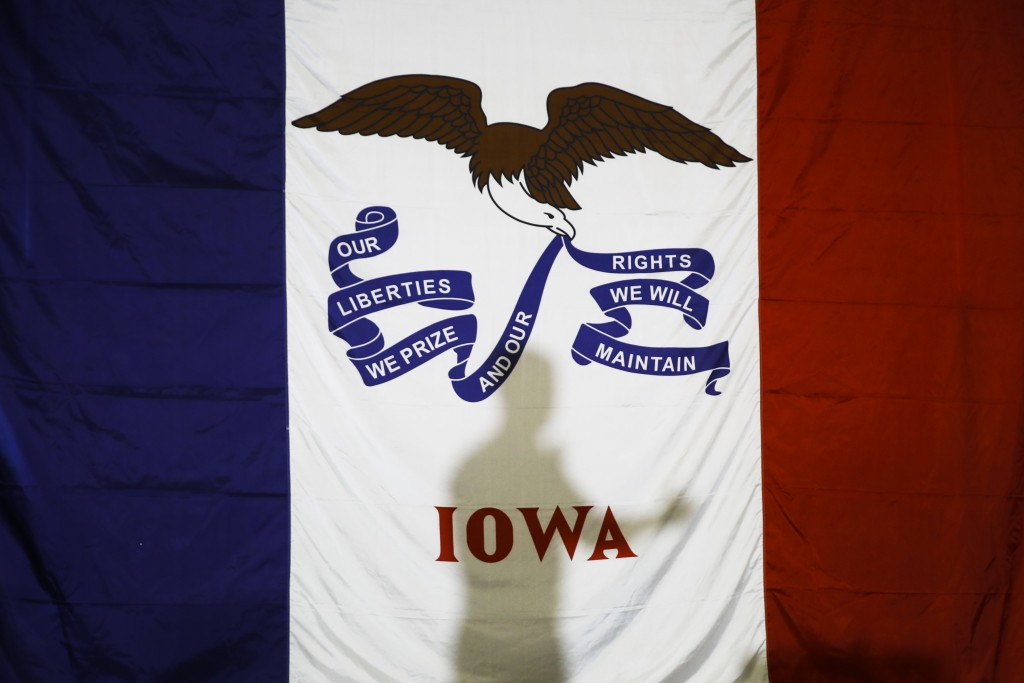 Democratic presidential candidate former South Bend, Ind., Mayor Pete Buttigieg's shadow is cast on the Iowa state flag as he speaks during a campaign...