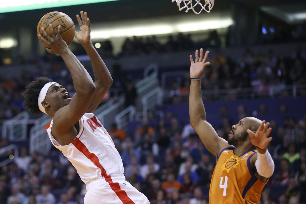 Houston Rockets forward Danuel House Jr., left, shoots over Phoenix Suns guard Jevon Carter (4) during the first half of an NBA basketball game Friday...