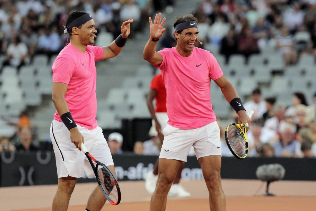 Trevor Noah and Rafael Nadal high five after winning a point against Roger Federer and Bill Gate in the exhibition match held at the Cape Town Stadium...
