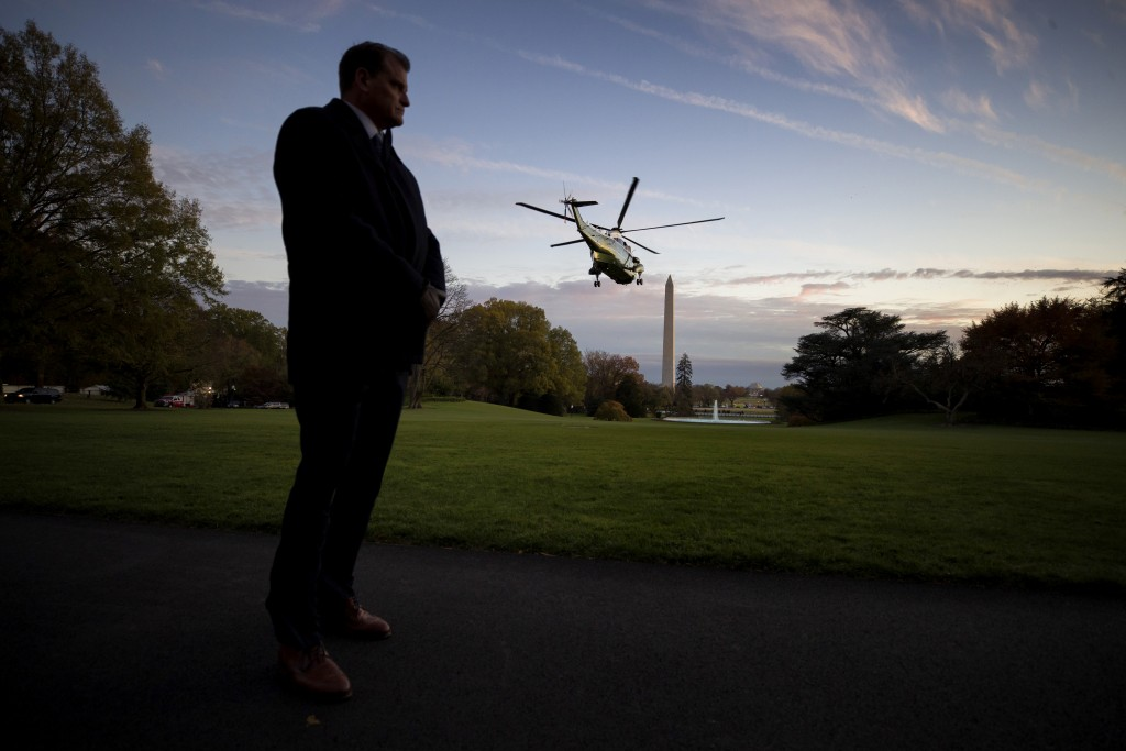 FIlE - In this Nov. 14, 2019, file photo a U.S. Secret Service special agent stands as Marine One, with President Donald Trump aboard, lifts off from ...
