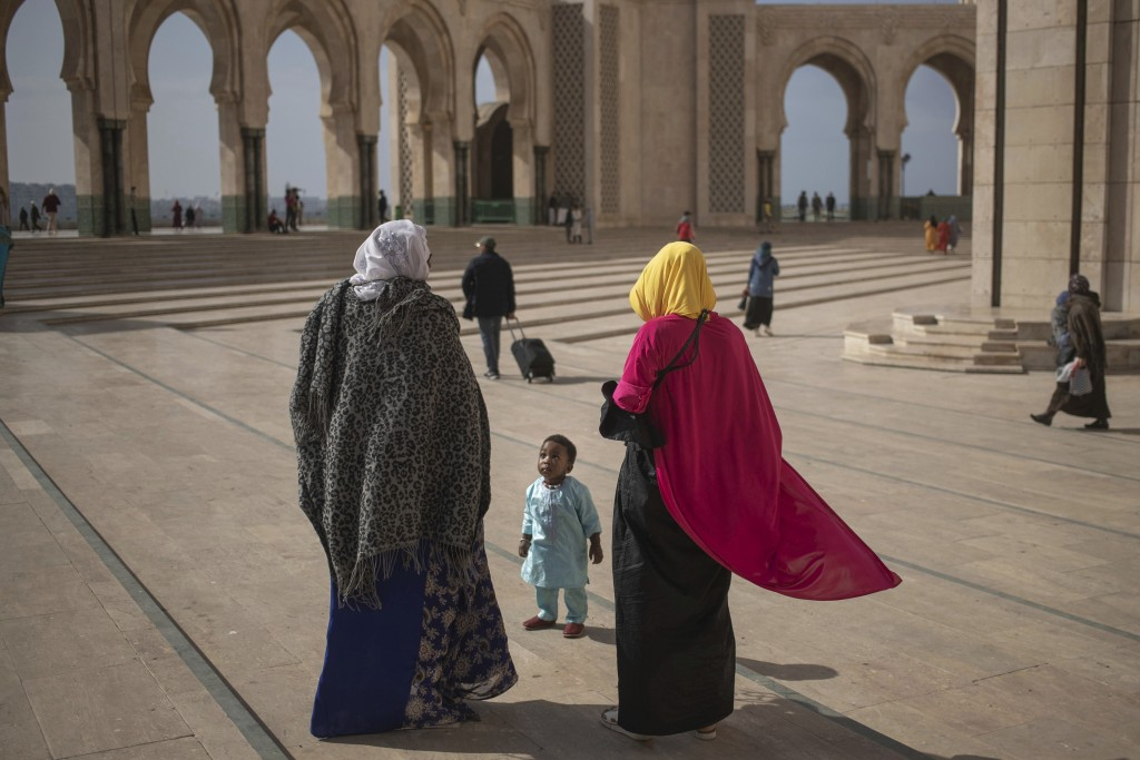 A Muslim family walks after Friday prayers outside the Hassan II mosque, one of the largest in Africa, in Casablanca, Morocco, on Friday, Feb. 7, 2020...