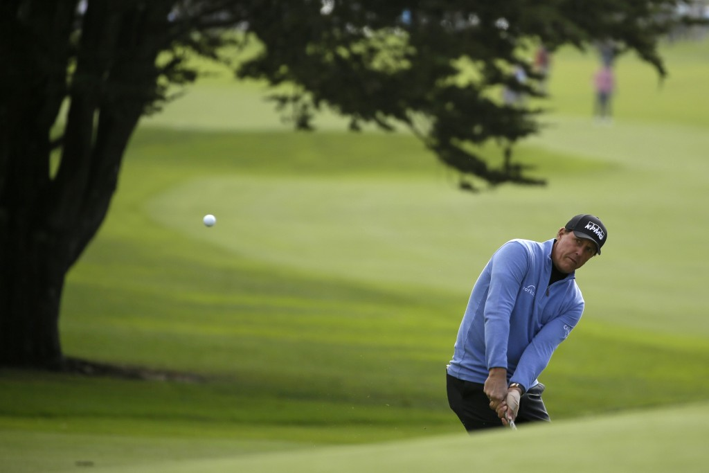 Phil Mickelson chips the ball on to the 14th green of the Pebble Beach Golf Links for a birdie during the third round of the AT&T Pebble Beach Nationa...