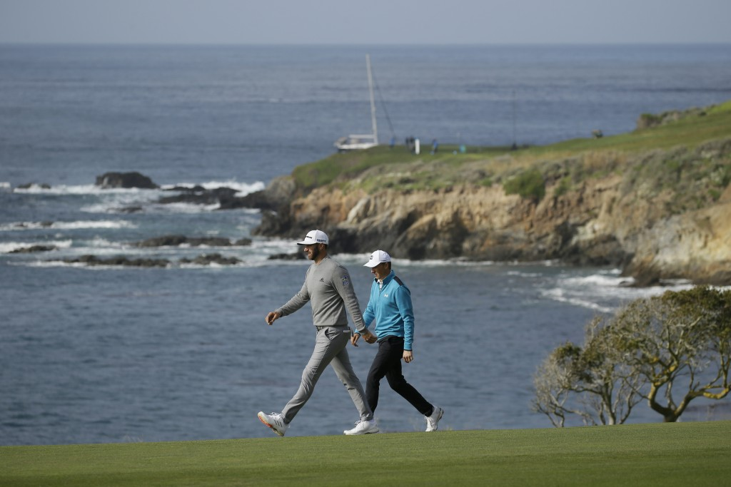 Dustin Johnson, left, and Jordan Spieth walk down the ninth fairway of the Pebble Beach Golf Links during the third round of the AT&T Pebble Beach Nat...