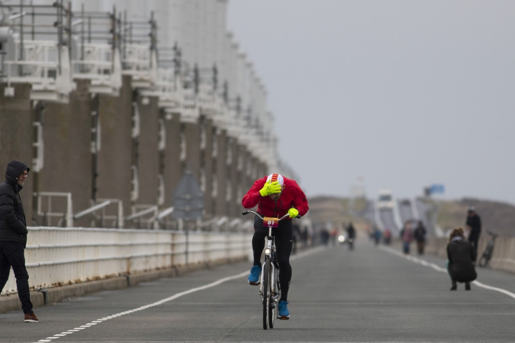 A competitor holds onto his cap as he battles gale force winds during the Dutch Headwind Cycling Championships on the storm barrier Oosterscheldekerin...