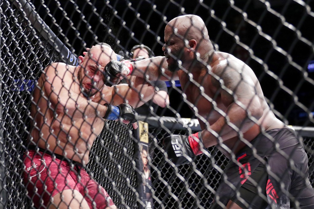 Derrick Lewis, right, hits Ilir Latifi during a heavyweight mixed martial arts bout at UFC 247 on Saturday, Feb. 8, 2020, in Houston. (AP Photo/Michae...
