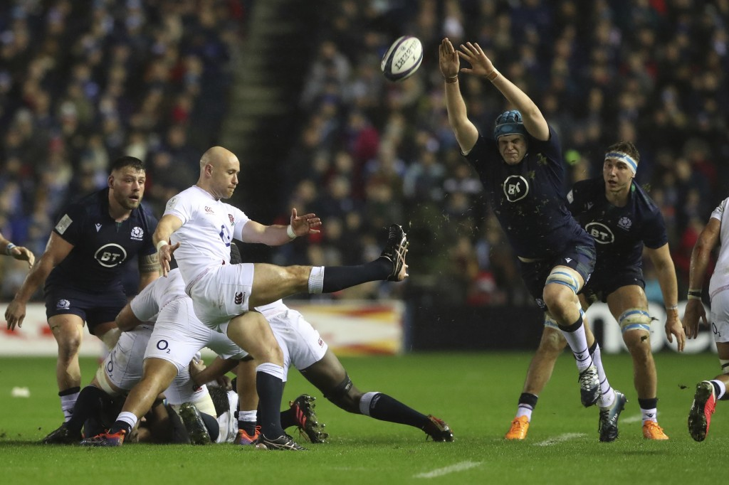 England's Willi Heinz, center, kicks the ball away as Scotland's Scott Cummings tries to charge it down during the Six Nations rugby union internation...