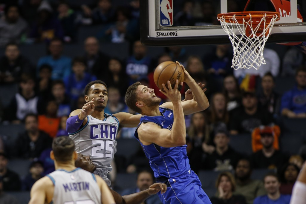 Dallas Mavericks forward Maxi Kleber, right, drives to the basket in front of Charlotte Hornets forward P.J. Washington (25) during the first half of ...