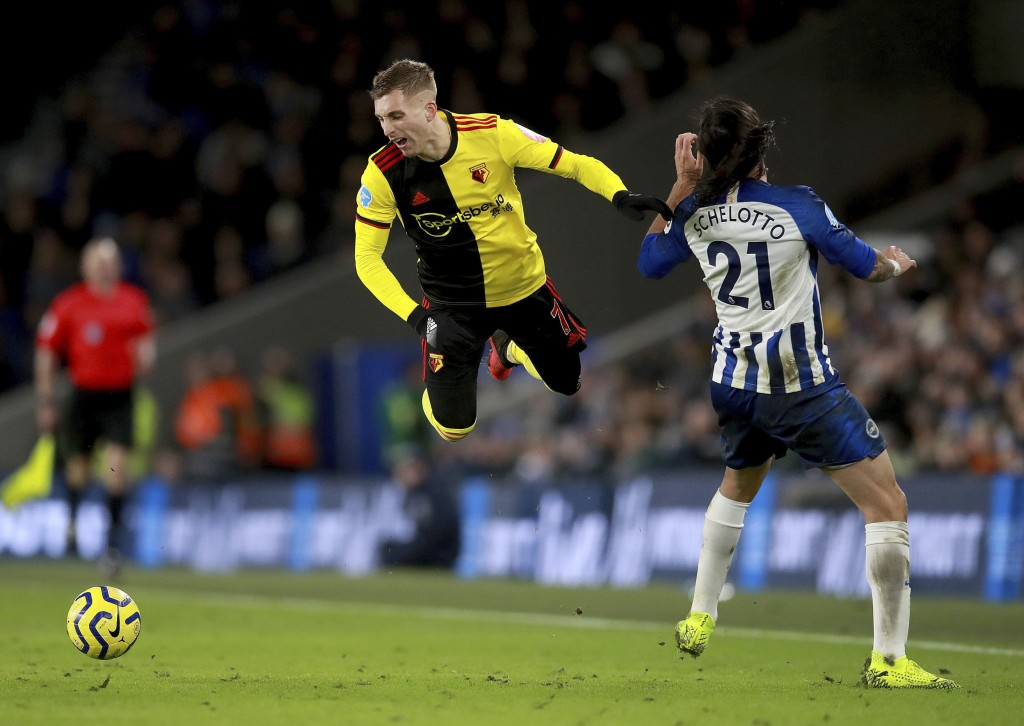 Watford's Gerard Deulofeu takes a tumble after a challenge from Brighton and Hove Albion's Ezequiel Schelotto, right, during the English Premier Leagu...